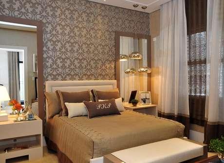 <p>A parede da cama conta com papel de parede de estampa adamascada e a cabeceira é lisa e em tom neutro. O projeto é da designer de interiores Patrícia Pasquini</p>