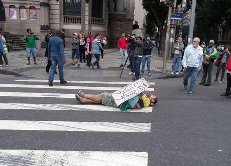"""<p>Com cartaz, manifestante se deita na faixa de pedestres em frente à Câmara e protesta: """"onde está o Amarildo?""""</p>"""