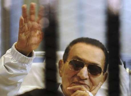 <p>Ex-presidente egípcio Hosni Mubarak acena para seus apoiadores de dentro de uma cela em uma corte de uma academia de polícia</p>