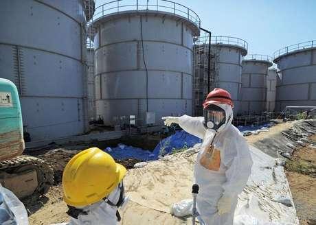 Ministro da Economia, Comércio e Indústria do Japão, Toshimitsu Motegi, usando traje de proteção e máscara, inspeciona tanques de água contaminada na usina nuclear avariada de Fukushima, no Japão. A Tokyo Electric Power Co, operadora da usina nuclear de Fukushima, disse que vai convidar especialistas estrangeiros para assessorá-la sobre a forma de lidar com a água altamente radiativa que está vazando do local, e o Japão sinalizou que pode utilizar um fundo de reserva para emergências de 3,6 bilhões de dólares para ajudar a pagar pela limpeza.