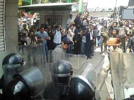 magen de un manifestante golpeando escudos de granaderos.