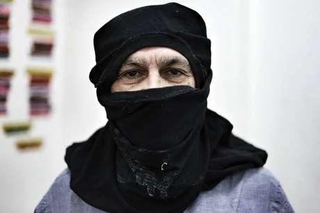 Caetano Veloso posa com o rosto coberto com uma camiseta, da mesma forma usada pelo grupo Black Bloc