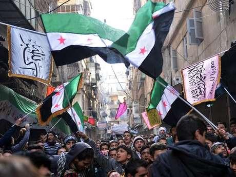 <p>Rebeldes marcham em Aleppo, cidade-berço da revolta síria,com a bandeirada Síria usada antes de Assad e adotada pela oposição ao regime</p>