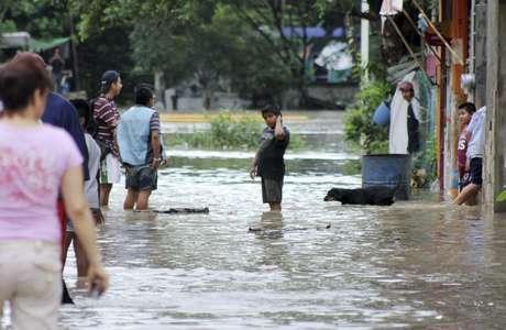 Moradores percorrem uma rua inundada em Poza Rica, no estado mexicano de Veracruz