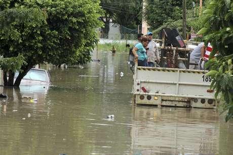 População afetada pela enchente viaja na parte de trás de um caminhão através de um bairro inundado em Poza Rica