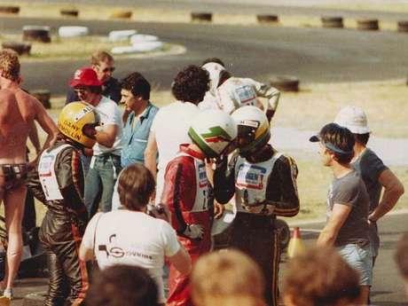 Terry Fullerton (macacão vermelho) conversa com Ayrton Senna (macacão preto) no Circuito de Jesolo, Itália, em 1979; Senna ainda corria com o capacete antigo, cinza com detalhes em verde e amarelo