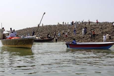 <p>La curiosidad lleva a la gente a usar botes para llegar a la isla surgida tras terremoto dePakistán.</p>