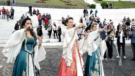 <p>Com trajes típicos, mulheres participam de sabrage coletivo na Festa do Espumante de Garibaldi, no Rio Grande do Sul</p>