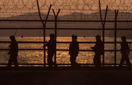 <p>Soldados fazem guarda na Zona Desmilitarizada (DMZ); ao fundo, o relevo da cidade de Paju, na Coreia do Sul</p>