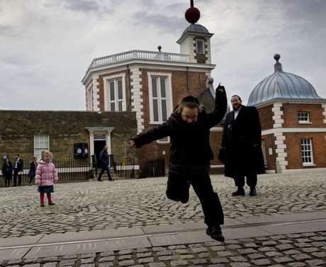 Criança pula sobre linha que representa a divisão do mundo em fusos horários no Observatório Real de Londres, em Greenwich