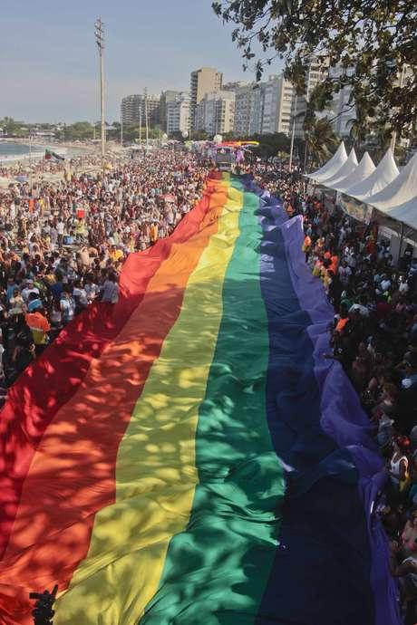 Público segura uma imensa bandeira com as cores do arco-íris durante a 18ª Parada LGBT