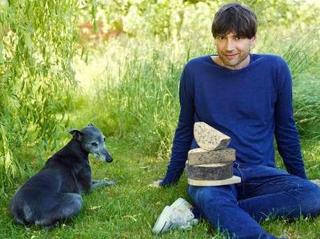 Alex James posa com queijo em sua fazenda, uma produtora artesanal