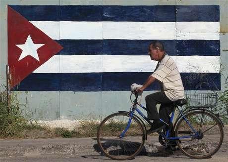 Ciclista passa em frente à bandeira cubana em Havana em imagem de dezembro de 2012
