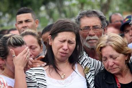 Viúva de PM morto em tiroteio chora durante sepultamento no Rio
