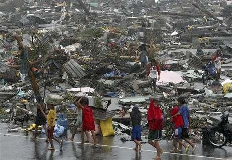 Sobrevivente carregam seus pertences em meio à destruição causada pelo supertufão Haiyan, que matou ao menos 10 mil pessoas nas Filipinas. 10/11/2013