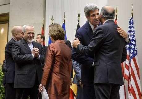 O chanceler iranino, Javad Zarif, sorri ao cumprimentar a chefe de relações exteriores da UE, Catherine Ashton, enquanto o secretário de Estado dos EUA, John Kerry, cumprimenta o chanceler francês, Laurent Fabius