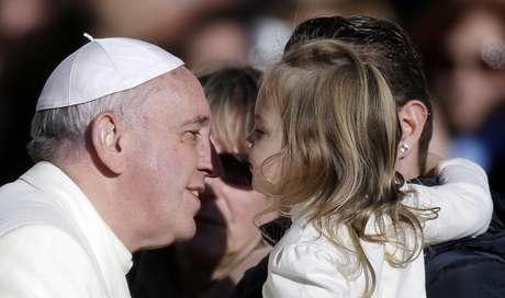 Papa interage com criança antes de sua audiência semanal na Praça São Pedro nesta quarta