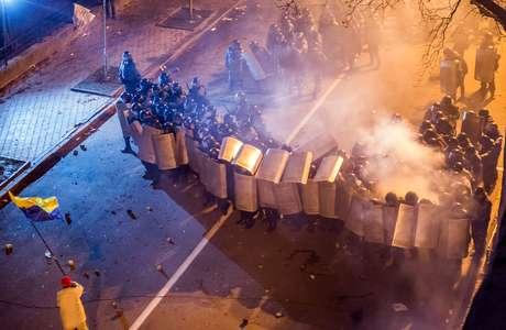 Manifestante agita bandeira ucraniana durante confrontos na capital Kiev