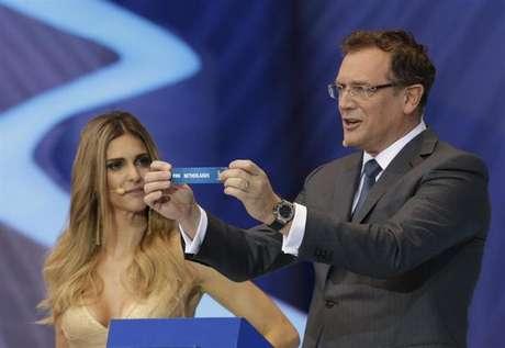 El secretario general de la FIFA, Jerome Valcke, sostiene el papel que muestra el nombre de Holanda junto a la presentadora Fernanda Lima durante el sorteo de la Copa del Mundo 2014 en Costa do Sauípe, en Sao Joao da Mata, estado de Bahía. 6 de diciembre, 2013.