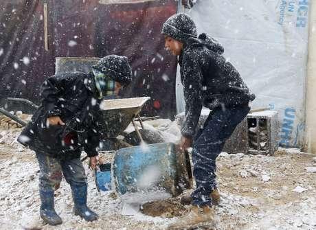 Crianças tentam carregar gás de cozinha em acampamento de refugiados montado na cidade de Zahle