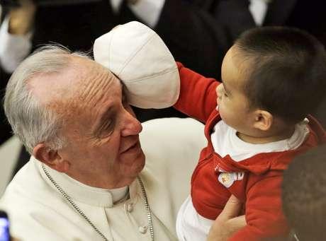 Criança brinca com o chapéu do Papa durante a audiência de sábado no Vaticano