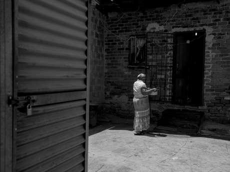<p>Mulher carrega panela com água para sua cada na favela de Alexandra, em Johannesburgo, na África do Sul. Água e o banheiro - porta do lado esquerdo -é dividido por cerca de250 moradias.</p>