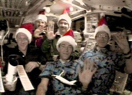 Tripulação do ônibus espacial Discovery comemorou o Natal de 1999 com gorros de Papai Noel