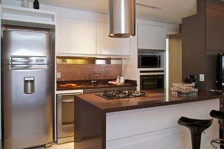 """<p><span style=""""text-align: -webkit-center;"""">A cozinha americana de 7m², projetada pela arquiteta Cinthia Garcia e a designer Andréia Karalkovas, conta com cores neutras e faixa de pastilhas metalizadas para contrastar com a sala. Apresenta coluna para o forno e micro-ondas, além de bancada com cook top. Informações: (11) 4224-2000</span></p>"""