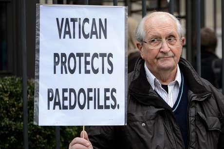 Homem exibe cartaz em protesto contra os casos de pedofilia no Vaticano em frente a sede da ONU em Genebra