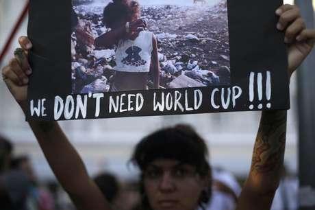 """Manifestante ergue cartaz durante um protesto contra a Copa do Mundo de 2014, em Copacabana, no Rio de Janeiro. Preocupado com o movimento """"não vai ter Copa"""" e com as críticas sobre a organização e os gastos para realização da Copa do Mundo, o governo prepara uma ofensiva com foco publicitário para reagir e transformar o evento em dividendo político para a presidente Dilma Rousseff, disse uma fonte do Executivo nesta sexta-feira. 25/01/2014."""