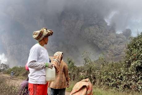 <p>Moradores observam a nuvem da erupção do vulcão</p>