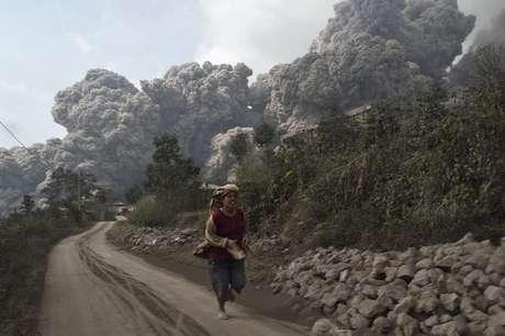 <p>Aldeão corre após o vulcão Monte Sinabung entrar em erupção neste sábado, na ilha ocidental de Sumatra</p>