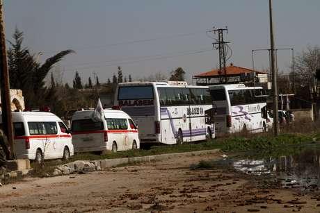 Famílias sírias deixam, em ônibus, a cidade de Homs, que virou um campo de batalha