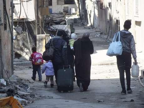 Civis levam seus pertences enquanto caminham até um ponto de encontro para serem evacuados da zona citiada de Homs