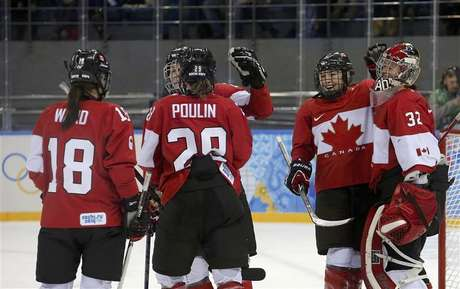 Canada's Catherine Ward, Marie-Philip Poulin, Jocelyne Larocque and goalie Charline Labonte celebrate after defeating Team USA in their women's preliminary round hockey game at the Sochi 2014 Winter Olympic Games February 12, 2014