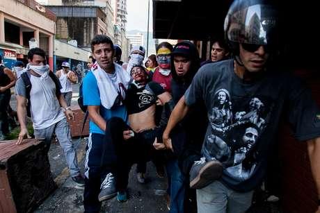 Estudante ferido é socorrido por manifestantes em Caracas