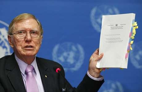Michael Kirby mostra cópia de seu relatório durante uma coletiva da ONU realizada nesta segunda-feira, em Genebra