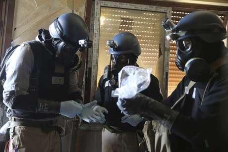 <p>Especialistas das Nações Unidas em armas químicas avaliam sacola plástica com amostras de um dos locais que sofreram um suposto ataque de armas químicas no bairro de Ain Tarma, em agosto de 2013</p>