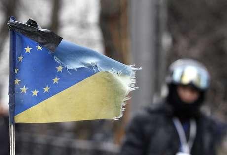 <p>Em gesto simbólico, uma fita preta foi colocada em uma bandeira que combina as bandeiras da Ucrânia e da União Europeia. A simbologia marca um dia de luto nas ruas de Kiev</p>