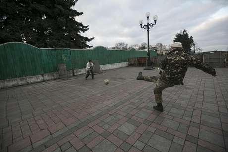 Manifestantes jogam futebol em frente a portão do Parlamento ucraniano