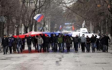 <p>Segurando uma bandeira russa, manifestantes marcham em frente ao prédio do governo, naCrimeia. De acordo com o Ministro do Interior ucraniano, a polícia está em alerta máximo depois que dezenas de manifestantes invadiram o edifício do Parlamento de Simferopol</p>