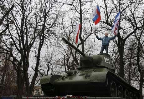 <p>Manifestante exibebandeiras da Rússia e da Crimeia em um antigo tanque das Forças Armadas da União Soviética, durante protesto em frente ao prédio do governo de Simferopol, na Crimeia</p>