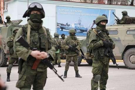 <p>Soldados armados, ao lado de veículos do exército russo, em frente aum posto de guarda de fronteira na cidade de Balaclava, na Crimeia, em 1 de março</p>