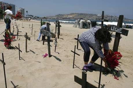 <p>Cruzes com nomes de vítimas da violência na Venezuela são fixadas nas areias da praia em Puerto La Cruz</p>
