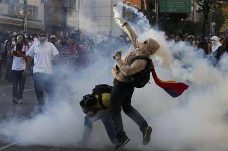 Un opositor al gobierno arroja una lata con gas lacrimógeno de la Guardia Nacional en Caracas, mar 2 2014. Criticado hasta por estrellas de Hollywood sobre la manera de lidiar con la ola de protestas antigubernamentales, el Gobierno de Venezuela se defendió el lunes ante la ONU acusando a los manifestantes de querer derrocar al presidente socialista Nicolás Maduro.