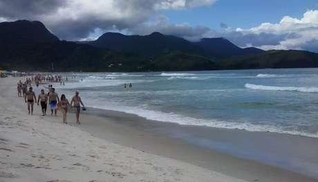 <p>De acordo com a Climatempo, o dia ser&aacute; de&nbsp;c&eacute;u nublado nesta segunda-feira no litoral paulista; na foto, banhistas caminham por praia de Maresias</p>