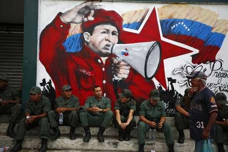 Soldados venezuelanos sentam em frente a um mural com a imagem de Hugo Chávez