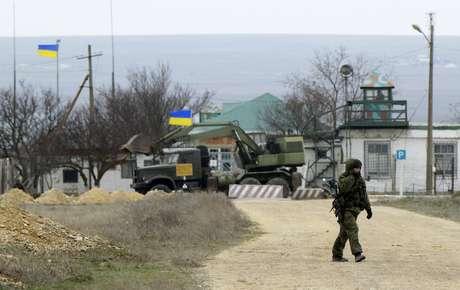 Homem armado, provável soldado russo, caminha próximo a base naval ucraniana no porto da Crimeia de Yevpatorva, neste sábado, 8 de março