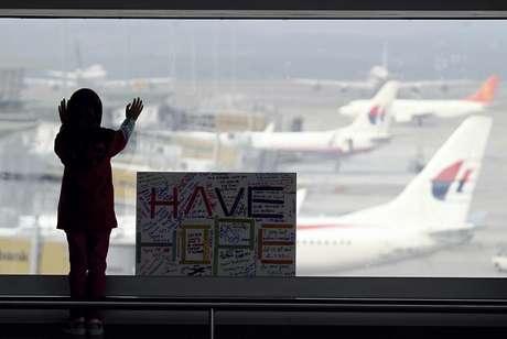 """Menina observa os aviões, ao lado de uma placa que diz """"temos esperanças"""", colocada no aeroporto internacional de Kuala Lumpur, na Malásia, nesta segunda-feira, 10 de março"""