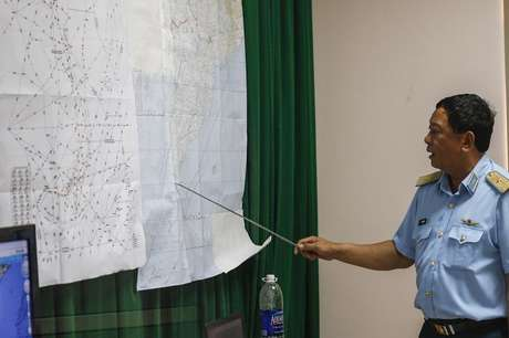O vice-comandante da Força Aérea vietnamita, Do Minh Tuan, indica pontos em um mapa durante uma coletiva de imprensa, após uma missão para encontrar o voo MH370 da Malaysia Airlines que desapareceu. Militares da Malásia acreditam que o avião que desapareceu há quase quatro dias com 329 pessoas a bordo voou por mais de uma hora após desaparecer das telas do controle de tráfego aéreo, alterando sua rota e viajando para oeste, sobre o Estreito de Malaca, segundo uma fonte militar graduada. 11/03/2014